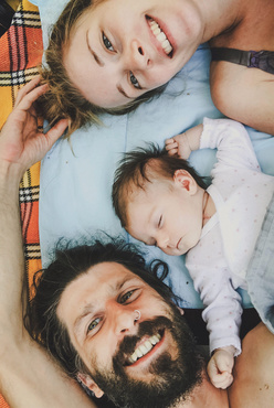 mom dad and baby lying on bed together